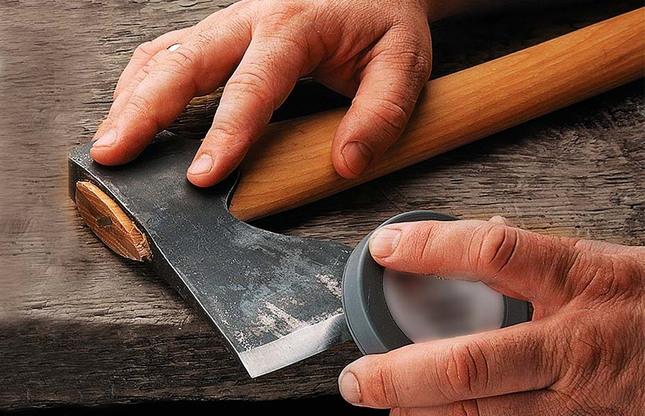 A man sharpens the blade of an ax with a sharpening stone